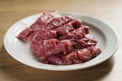 Slices of raw beef in white plate on kitchen table. Closeup photo Royalty Free Stock Photo