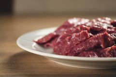 Slices of raw beef in white plate on kitchen table. Closeup photo Stock Photography