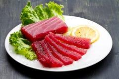 Slices of raw bluefin tuna  sashimi on white dish on wood backgr Royalty Free Stock Photos
