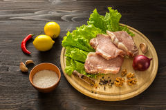 Slices of raw meat. Pork escalope on a wooden board. Stock Image