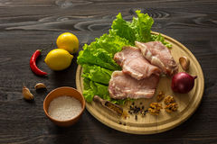 Slices of raw meat. Pork escalope on a wooden board. Royalty Free Stock Photos