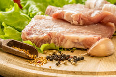 Slices of raw meat. Pork escalope on a wooden board. Royalty Free Stock Images
