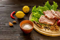 Slices of raw meat. Pork escalope on a wooden board. Royalty Free Stock Image