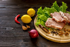 Slices of raw meat. Pork escalope on a wooden board. Stock Photos