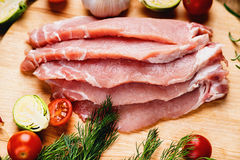 Slices of raw pork meat and vegetables. Slices of raw pork meat and colorful vegetables Royalty Free Stock Images