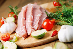 Slices of raw pork meat and vegetables. Photography of a slices of raw pork meat and vegetables Stock Photos