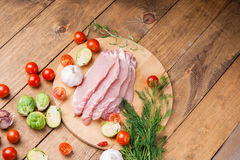Slices of raw pork meat and vegetables. On wooden background Royalty Free Stock Photography