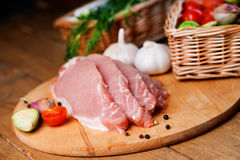 Slices of raw pork meat and vegetables. On a wooden cutting board Royalty Free Stock Image
