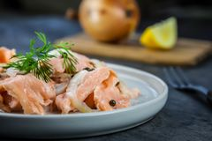 Slices of raw salmon marinated in lemon with green pepper and onion Stock Image