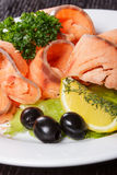 Slices of red fish with lemon and olives on plate Royalty Free Stock Images