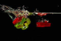 Slices of red and green peppers falling in water Stock Images