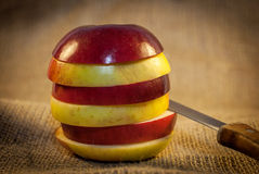 Slices of red and yellow apples with knife Stock Photography