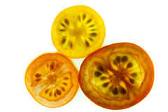Slices of red, yellow, and orange grape tomatoes o. Three slices of red, yellow, and orange grape tomatoes isolated on a white background stock image