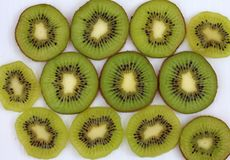 Slices of ripe and juicy kiwi ON white surface. Lots of green slices of ripe and juicy kiwi ON white surface Stock Images