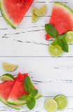 Slices of ripe juicy organic watermelon on old wooden table, served with fresh lime and mint leaves. Watermelon mojito ingredients Royalty Free Stock Images