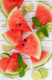 Slices of ripe juicy organic watermelon on old wooden table, served with fresh lime and mint leaves. Watermelon mojito ingredients Stock Photos