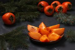 Slices of ripe orange persimmon are on a wooden plate against stock photography