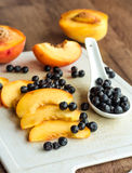 Slices of ripe peach on a white board, green knife Royalty Free Stock Image