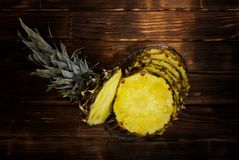 Slices of ripe pineapple in a transparent plate on a wooden back stock image