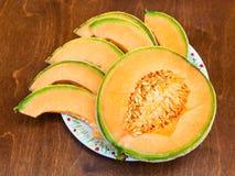 Slices of ripe sicilian cantaloupe melon on table Stock Photo