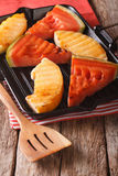 Slices of ripe watermelon and melon in a pan grill closeup. vert Stock Photos