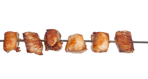 Slices of roast meat on a skewer. On white background royalty free stock photo