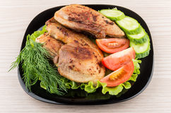 Slices of roast pork with salad, tomatoes, cucumbers in plate Stock Image