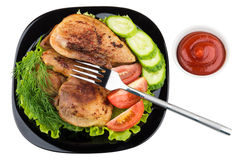 Slices of roast pork with salad, tomatoes, cucumbers in plate Stock Photo