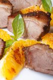 Slices of roasted duck meat with orange macro on a white plate Stock Photos