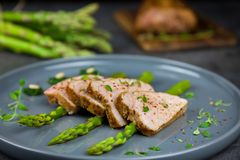 Slices of roasted pork tenderloin on asparagus with pesto from kale and thyme on the grey plate Royalty Free Stock Photo