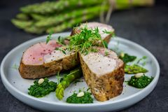 Slices of roasted pork tenderloin on asparagus with pesto from kale and thyme on the white plate Royalty Free Stock Image