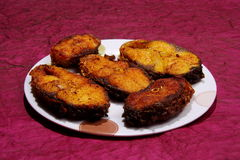 Slices of Rohu fish fry over maroon paper Stock Photo