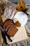 Slices of rye bread, camembert, honey and knife on a board Stock Photography