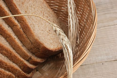 Slices of rye bread and ears of corn in basket Stock Images