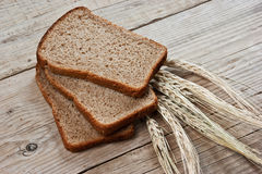 Slices of rye bread and ears of corn Stock Photos