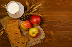 Slices of rye bread, a jug of milk, apples and ears of corn on sackcloth Royalty Free Stock Photo