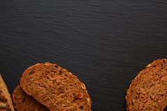 Slices of rye bread with pumpkin seeds on plate, board, tray of. Black slate Royalty Free Stock Photos