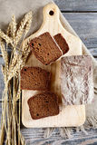Slices of rye Bread with spikelets of wheat on a cutting board Stock Photos