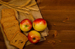 Slices of rye bread, three apples, ears of wheat on sacking, wooden table Stock Photography
