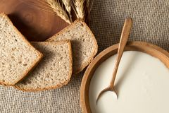 Slices of rye bread on a wooden plate, honey in the old porcelain bowl, milk, sour cream stock photo