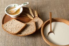 Slices of rye bread on a wooden plate, honey in the old porcelain bowl, milk, sour cream royalty free stock photo