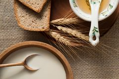 Slices of rye bread on a wooden plate, honey in the old porcelain bowl, milk, sour cream stock images