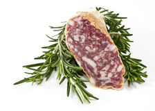 Slices of salame and rosemary Royalty Free Stock Photography