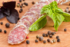 Slices of salami, basil and pepper. Focus on foreground Stock Image