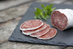 Slices of salami on natural wooden Royalty Free Stock Photo