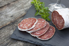 Slices of salami on natural wooden Royalty Free Stock Images