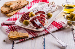 Slices of salami on a white plate Stock Image