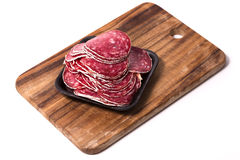 Slices of salami on wooden board Stock Photos