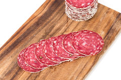 Slices of salami on wooden board Royalty Free Stock Photos