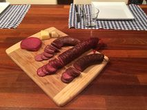 Slices of Salami on a wooden plate. On a table Stock Photo